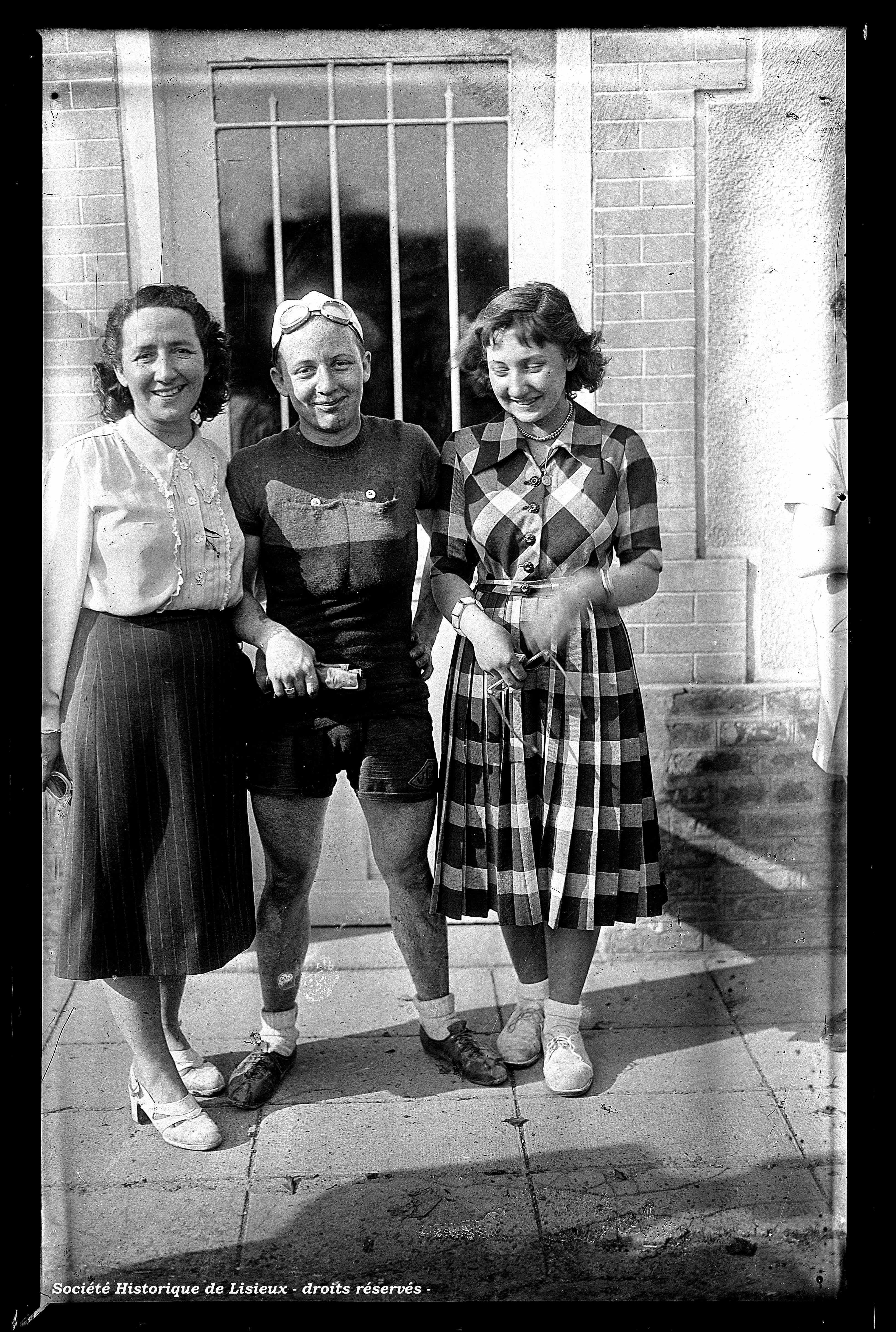 Coureur cycliste entouré de 2 jeunes femmes